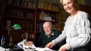 en man och en kvinna tittar på gamla bilder