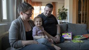 Familj bestående av mamma, pappa och barn sitter i en soffa. Barnet ler mot kameran. På soffan syns barnets leksaker.