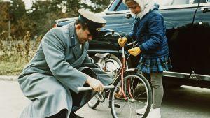 Juri Gagarin pumppaa pyöränrengasta tyttären seuratessa vierestä.