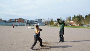 En person håller på att svinga ett bobollsträ och en annan slänger boll i luften.