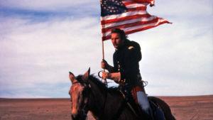 Mies ratsastaa Amerikan lipun kanssa.
