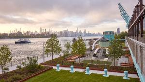Färgglad marknadsföringsbild från byggnadsbolaget över Domino Park med utsikt mot Manhattan