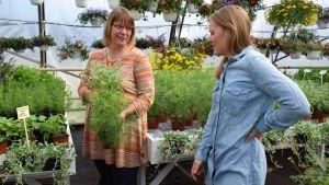 Annika Järvinen-Wikström och Stella Törnroth står mitt bland blommor och växter.