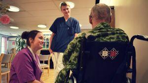 Matilda och Abbe talar med en äldre person som sitter i en rullstol i Almahemmet.