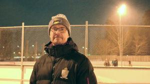 Porträttfoto av man som står framför en ishockeyrink. Mannen har mössa, glasögon och dunjacka. Det är vinter och mörkt ute.