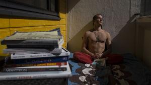 En ung man sitter på en balkong och njuter av solen. Han har ögonen fast. På bilden ser man även en trave böcker.