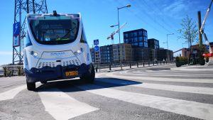 En förarlös buss kör längs med stranden i Fiskehamnen i Helsingfors.