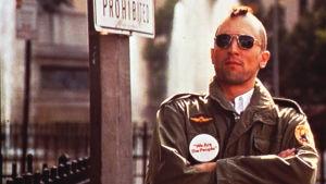 Travis Bickle (Robert de Niro) maiharitakissaan, aurinkolaseissaan ja irokeesikampauksessaan elokuvassa Taksikuski