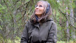 Anneli Jussila ser upp mot trädens kronor i en grön vårskog.