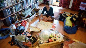 Sanna-Mari Kunttu sitter på golvet i sitt vardagsrum med en karta, omgiven av väskor, lådor och packning inför deras paddlingsexpedition.