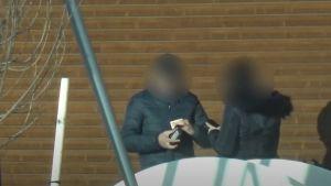 Två personer med svarta rockar. Den ena sätter sedlar i plånboken.