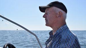 Börje Holmberg sitter i sin båt och ser ut över ett somrigt hav.