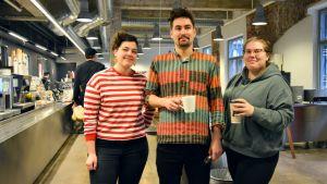 studerande poserar i en studentrestaurang, en man och två kvinnor