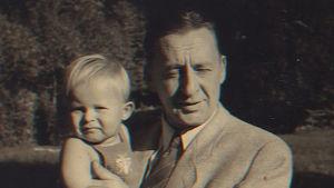 Nuori Hannu Hallamaa isänsä sylissä vanhassa valokuvassa.