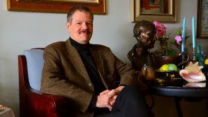 en man sitter i brun murrig kostym i en fåtölj