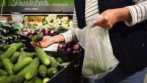 En kvinna plockar gurka i sin påse i matbtutiken.