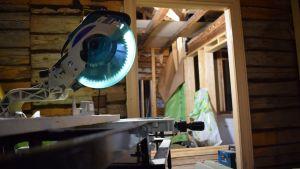 En cirkelsåg på ett sågbord i ett stockhus som håller på att renoveras.