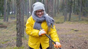 Minna Söderholm i gul regnjacka i en skog med en kratta i händerna.
