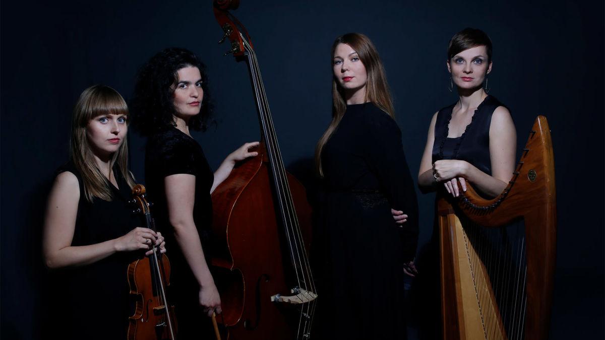 På bilden finns medlemmarna i den isländska kvartetten Umbra Ensemble. De håller sina instrument violin, cello och harpa på bilden som har en mörk bakgrund.