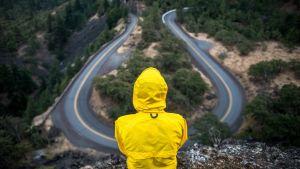 ihminen keltaisessa tarkissa katsoo alhaalla kiemurtelevaa tietä