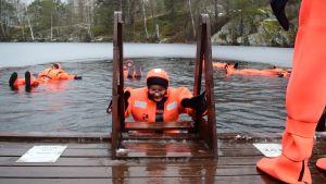 Flera personer flyter omkring i en isvak i lysande orangea torrdräkter, en person håller på att klättra ner för stegen.
