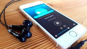 Telefon med hörlurar. Yle Vegas direktsändning öppen via Arenan-appen på telefonen.