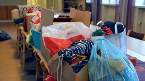Påsar och lådor med kläder och leksaker på ett bord.