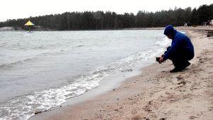 man på strand med kamera