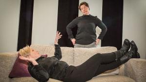 Två kvinnor i medelåldern, den ena ligger på en soffa och den andra står