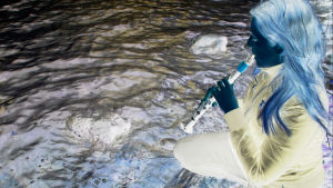 Kuvituskuva. Nainen soittaa huilua veden äärellä. Käsitelty negatiivikuva.