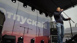 Aleksei Navalnyi seisoo esiintymislavalla mikrofoni kädessä.