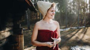 Nainen saunan pihalla pyyhkeessä ja saunamyssyssä.