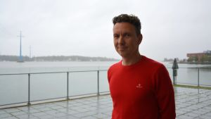 En vit man med röd tröja står framför vattnet.