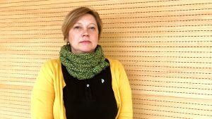 en kvinna med neutral min står i gula kläder framför en trävägg