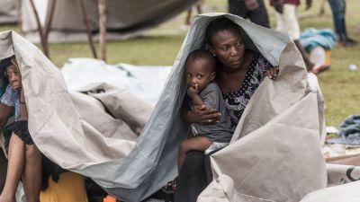 En kvinna och ett barn tar skydd under presenning i Haiti.