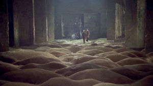 Kaksi miestä suuressa tyhjässä teollisuusrakennuksessa, jonka lattiaa peittävät hiekkadyynejä muistuttavat muodostumat. Kuva elokuvasta Stalker