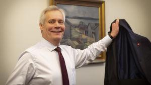 En man står med en kavajjacka i handen framför en oljemålning och ser glad ut.