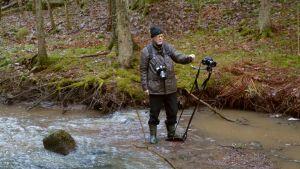 Jan Fröjdman står mitt i bäcken och fotograferar med ett stativ. Han har stövlar och ser koncentrerad ut.
