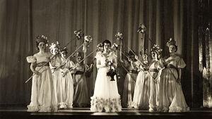 Sopraano Anna Mutanen operetin Vetoketju pääroolissa kukkaistyttöjen ympäröimänä Viipurin teatterissa noin vuonna 1937.
