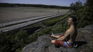 En ung man sitter på en bergsavsats och håller i en klättringslina.Han har bar överkropp och en klättringssele på sig.