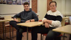 Atte Hellbom och Joacim Oksanen sitter i ett klassrum med armarna vilande på var sin pulpet.