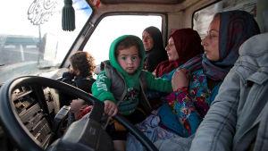 Tre syriska kvinnor och två barn i en bil.