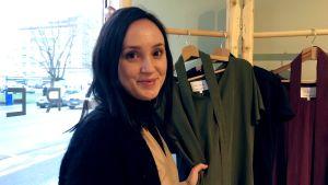 en kvinna som står bredvid några klädesplagg