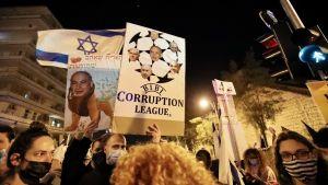 Demonstranter visar sitt missnöje mot Benjamin Netanyahu - en skylt visar Netanyahu som del av ett korruptionsnätverk. En korruptionsrättegång mot Netanyahu pågår i Israel.
