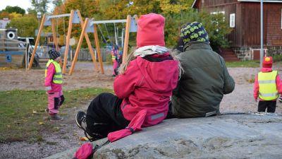 Två barn, en flicka och en pojke, sitter på ett berg, med ryggen mot kameran. I bagrunden syns lekande barn som har gula reflexvästar på sig.