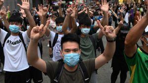 Demonstranter med munskydd och händerna upphöjda.