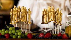 Oscar-patsaita koristeena, viinirypäleitä ja mansikoita edessä