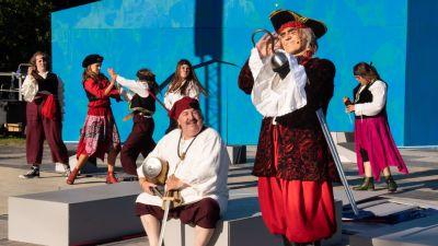 Karri Kaksonen som Kapten Krook står och beundrar sin krok och Peter Kuvaja som hans bullriga kumpan sitter bredvid och skrattar. I bakgrunden slåss pirater.