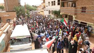 Människor viftar med Sudans flagga och protesterar. En man står på en buss och fotograferar demonstrationen.