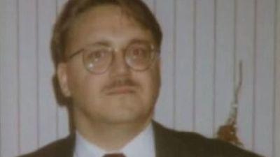 En man i mustasch och runda glasögon på en grynig gammal bild..